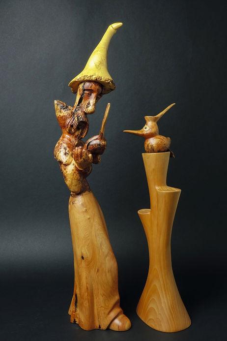 Magicien barbu, baguette en main, qui dialogue avec son drôle d'oiseau. Sculpture en bois de Christian Delacoux, h 63 cm.