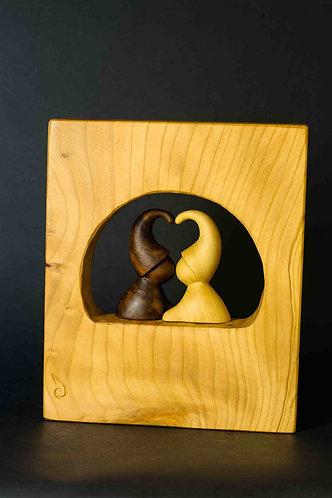 Deux lutins s'embrassent nichés dans une fenêtre ronde. Sculpture en bois de Christian Delacoux, h 27 cm.