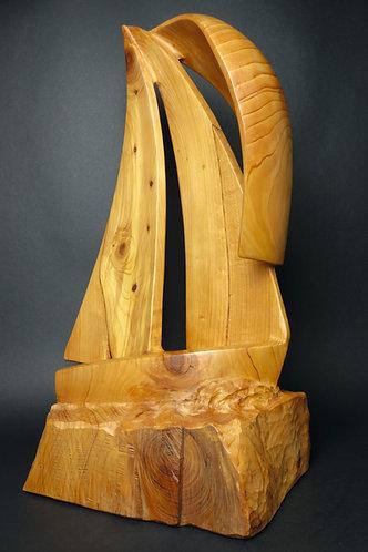 Un voilier poussé par les vents fend les flots. Sculpture en bois de Christian Delacoux, h 69 cm.