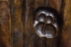 Empreinte de couple au dos de la sculpture de Christian Delacoux symbolisant une forêt. Bronze marron sur fond cuivré.