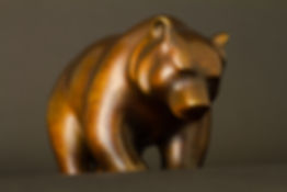 Ours en marche.  Sculpture en bronze marron sur fond cuivré de Christian Delacoux, longueur 25 cm.