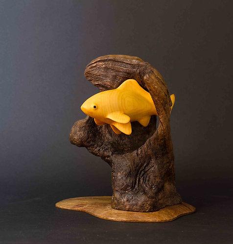 Poisson jaune qui passe par un trou dans un récif. Sculpture en bois de Christian Delacoux, h 25 cm.