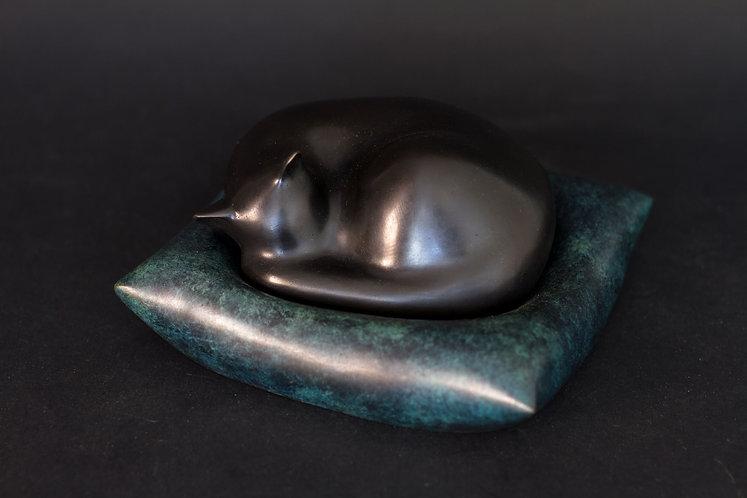 Chat noir dormant sur son coussin bleu moucheté. Sculpture en bronze de Christian Delacoux, longueur 16 cm.