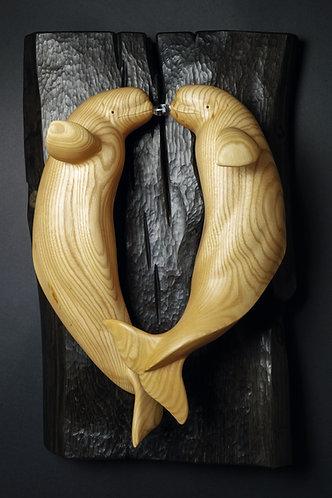 Deux bélugas sur un fond noir se font face et produisent une bulle commune. Sculpture en bois de Christian Delacoux, h 60 cm.