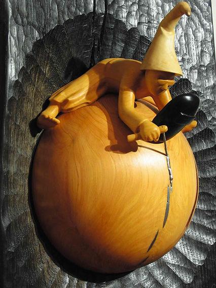 Magicien à califourchon sur la terre qu'il restaure par soudures. Sculpture en bois de Christian Delacoux, h 115 cm.