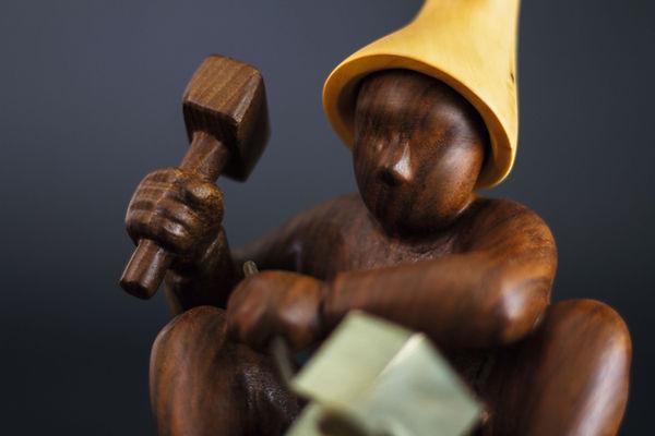 Détail lutin assis entrain de dégager une pyrite. Sculpture en bois de Christian Delacoux, h 19 cm.