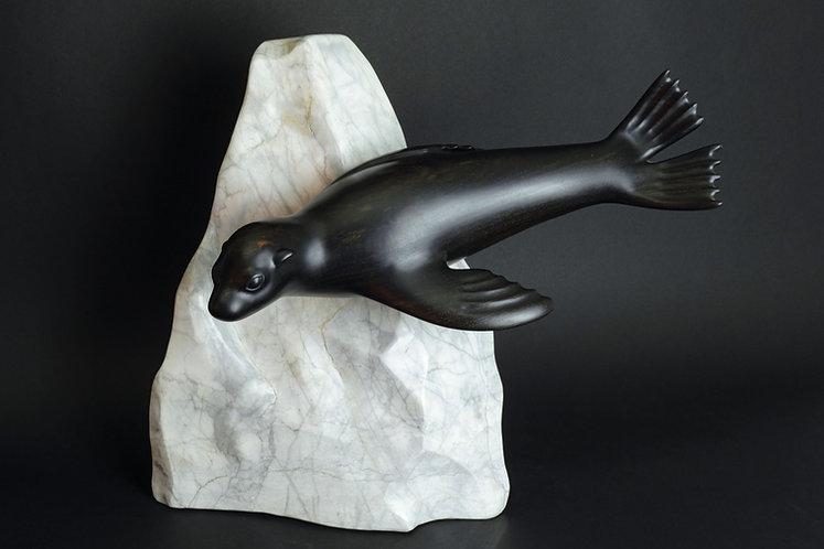 Une jeune otarie en ébène nage au ras d'un iceberg. Sculpture en bois et pierre de Christian Delacoux, h 46 cm.