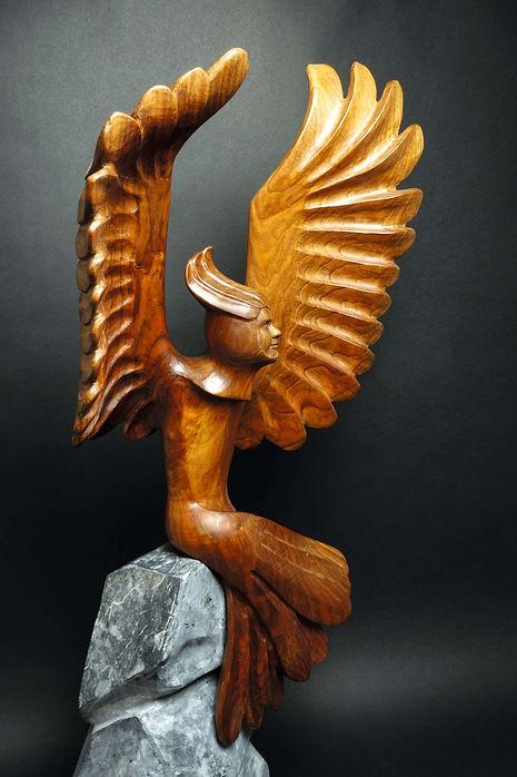 Homme ailé sur son perchoir rocheux. Un messager porteur de bonnes nouvelles. Sculpture en bois de Christian Delacoux.