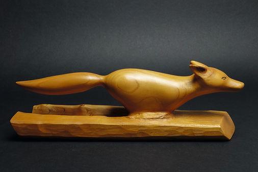 Renard qui court à toute allure dans la neige poudreuse. Sculpture en bois de Christian Delacoux, longueur 30 cm