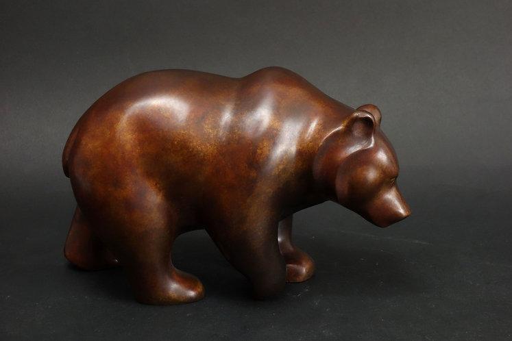 Ours cheminant tranquillement. Sculpture en bronze marron sur fond cuivré de Christian Delacoux, longueur 25 cm.