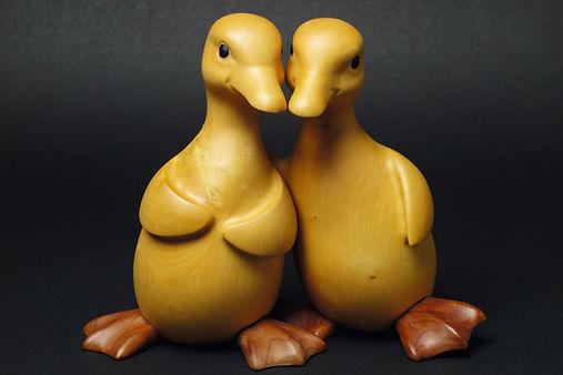 Deux cannetons jaunes qui se serrent tendrement l'un contre l'autre. Sculpture en bois de Christian Delacoux, h 17 cm.