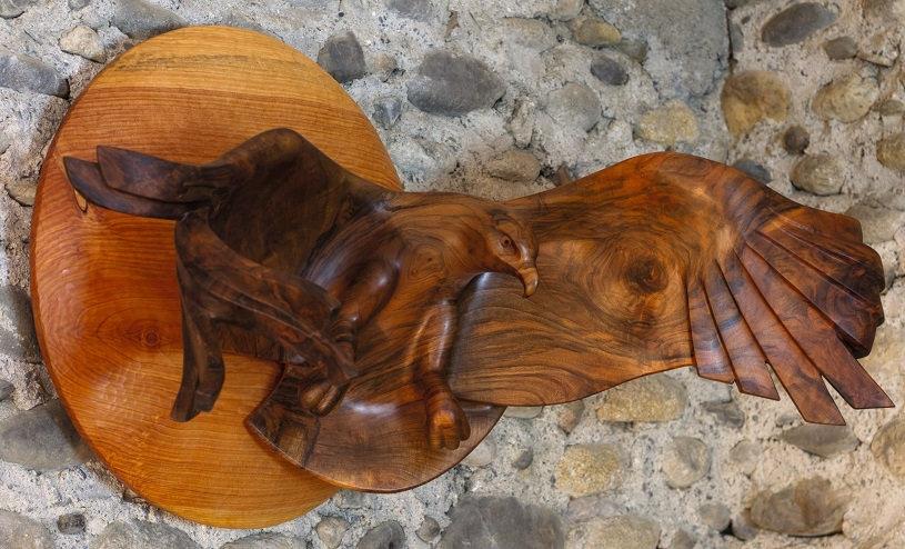 Aigle royal aux ailes déployées chassant le soleil dans le dos. Sculpture en bois de Christian Delacoux, 98 cm de large.