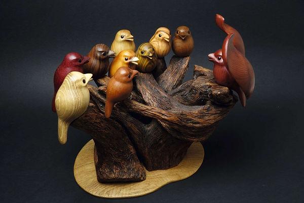 Chorale d'oiseaux autour de son chef de chœur. Sculpture en 12 essences de bois de Christian Delacoux, h 32 cm.