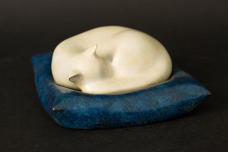 Chat blanc dormant sur son coussin bleu moucheté. Sculpture en bronze de Christian Delacoux, longueur 16 cm.