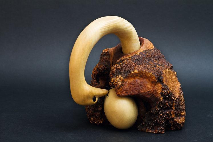 Une autruche se penche vers son œuf où apparaît un petit bec. Sculpture en bois de Christian Delacoux, h 20 cm