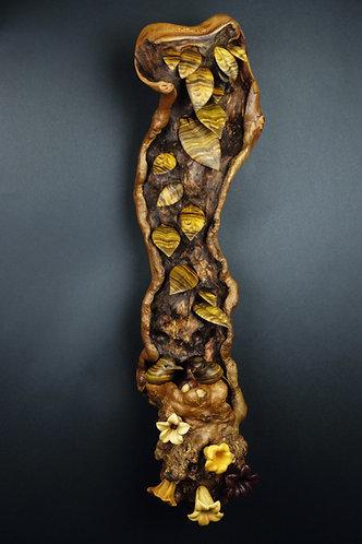 Deux petits oiseaux ont élu domicile dans une branche feuillue et fleurie. Sculpture en bois de Christian Delacoux, h 82 cm.