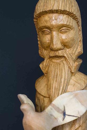 Un fin personnage barbu au visage paisible porte une colombe. Sculpture en bois de Christian Delacoux, h 86 cm.