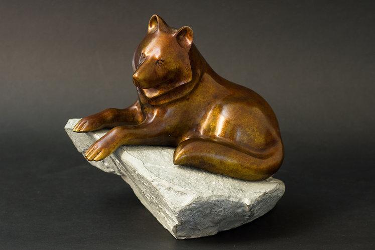 Loup brun allongé sur un rocher. Sculpture en bronze de Christian Delacoux, h 21 cm