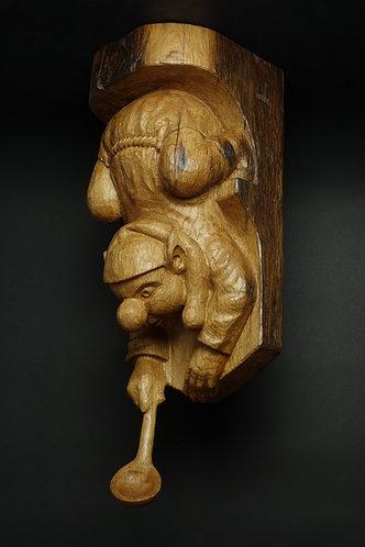 Lutin se penchant dans le vide pour attraper quelque chose avec sa cuillère. Sculpture en bois de Christian Delacoux.