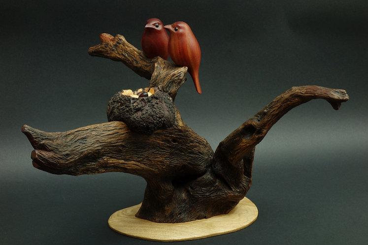 Deux oiseaux sur un arbre à côté d'un nid contenant trois œufs. Sculpture en bois de Christian Delacoux, h 40 cm.
