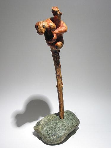 Paresseux imaginaire agrippé à son arbre planté dans une pierre. Sculpture en bois de Christian Delacoux, h 45 cm.