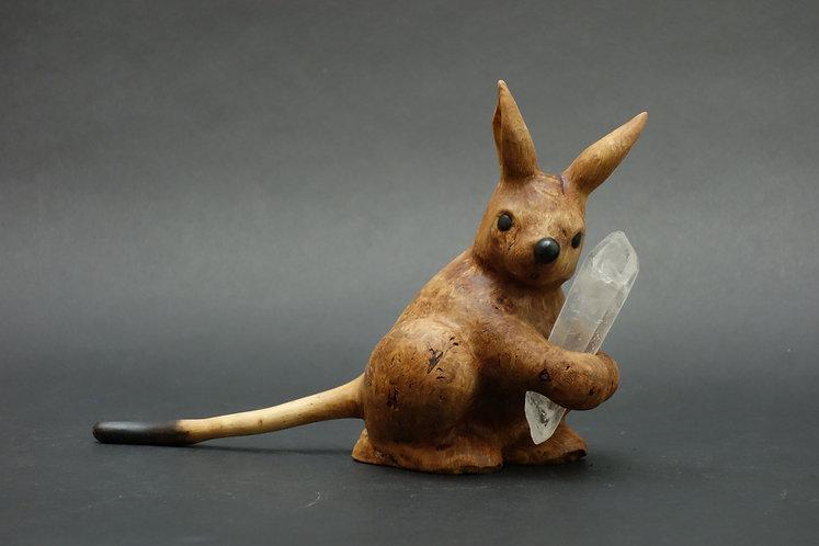 Un lièvre sauteur tient du quartz. Sculpture en bois de Christian Delacoux, 14 cm de hauteur.