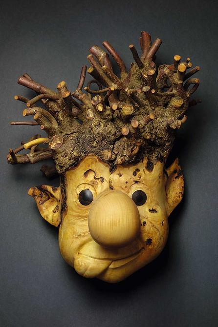 Troll au gros nez et aux cheveux ébouriffés  qui tire la langue. Sculpture en bois de Christian Delacoux, h 52 cm.