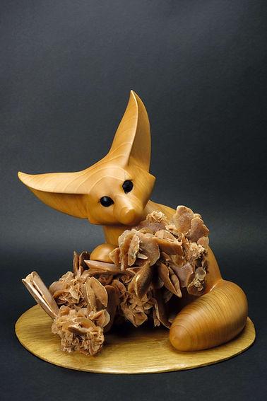 Fennec caché derrière une grosse rose des sables. Sculpture en bois de Christian Delacoux, h 33 cm