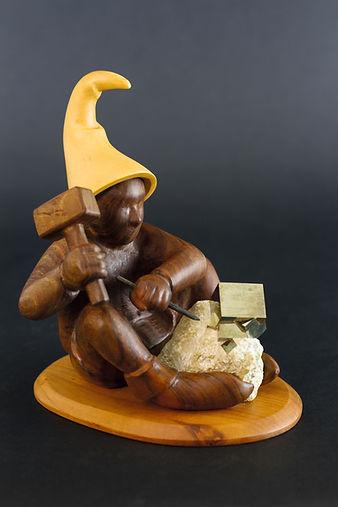 Lutin assis entrain de dégager une pyrite. Sculpture en bois de Christian Delacoux, h 19 cm.