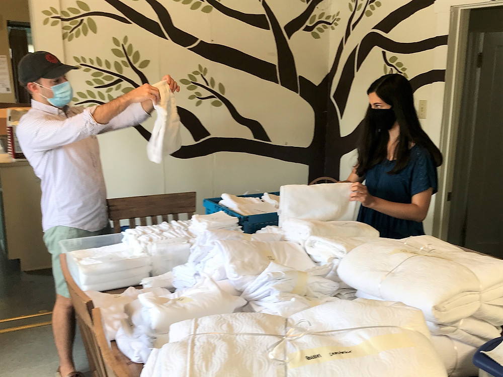 Shelter director Chase Techentin and intern Lucia Davila sort and fold a small part of the bed and bath linens donated by Home2 Suites Bloomington