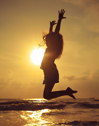 Happy girl jumping on the beach in sunse
