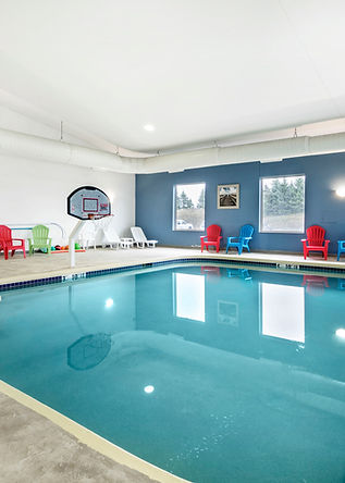 Pool area at Comfort Suites hotel of Par 4 Resorts in Waupaca Wisconsin with basketball hoop, kiddie pool, and pool chairs for kids and adults