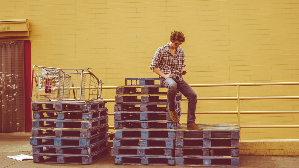 Man sitting on a crate of pallets