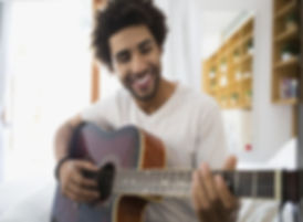 smiling-man-playing-guitar-in-bedroom-he