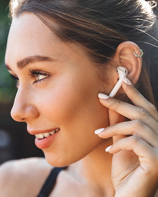 Close up portrait of a lovely young fitness girl listening to music through wireless earph