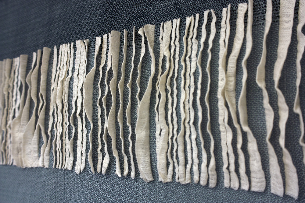 Detail of woven pleats, white pleats on gray and dark gray background.