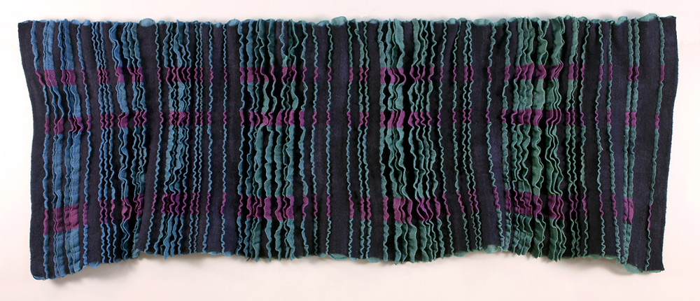 Woven work with surface pleating.  Pleats also have 3 horizontal stripes in magenta.
