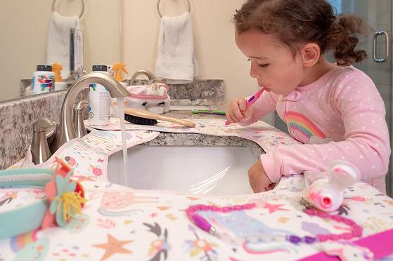 Girl brushing teeth at sink with unicorn print bathroom countertop protector