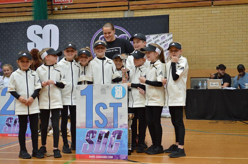 DIS sponsored Mini D-fuse dance team receiving trophy