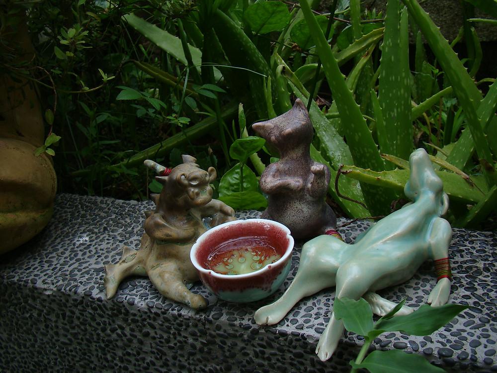 Three ceramic animal having a drinking party