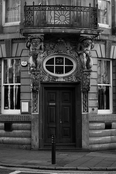 Monochrome image of doorway with stone carvings below a balcony.