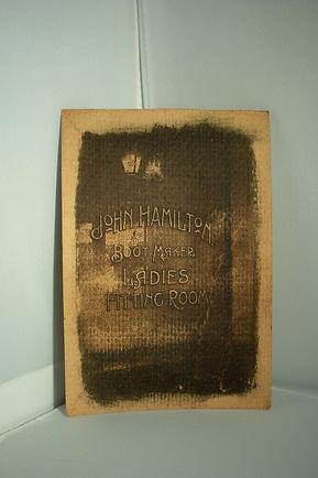 sepia toned shop window reading John Hamilton Boot Maker Ladies Fitting Room