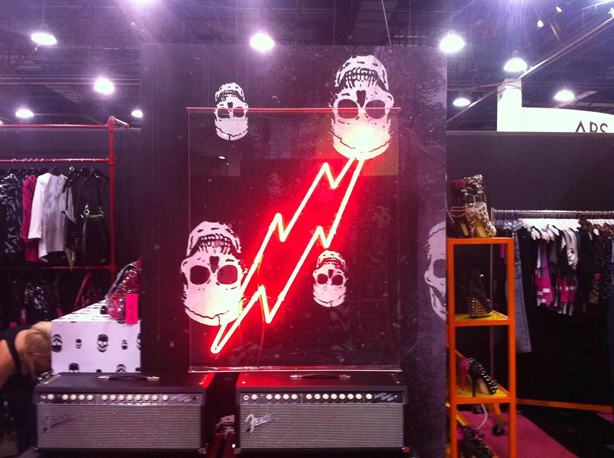 Custom neon lightening bolt for trade show with skull print backdrop