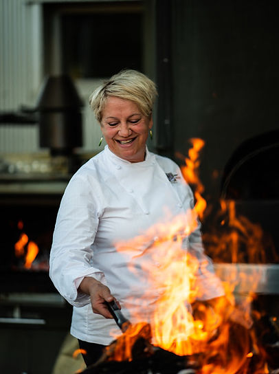 Chef Barbara Alexander cooks outside over an open flame.