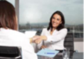 women-shaking-hands-at-desk.jpg 2015-10-