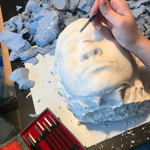 Artist using carving tools to clean up plaster face cast.
