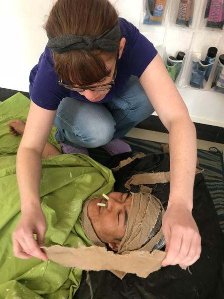 Artist Amanda Porter putting burlap strips on a models face for a face casting.