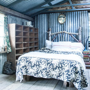 Bespoke green wood bed contrasts with corrugated iron.