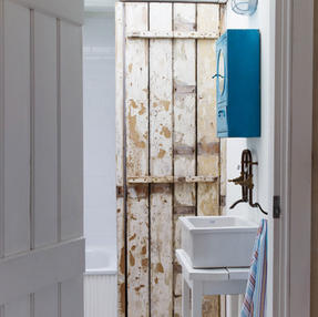 Reclaimed wood doors give texture individuality to this bathroom
