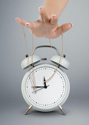 Hand puppeteer manipulating alarm clock,